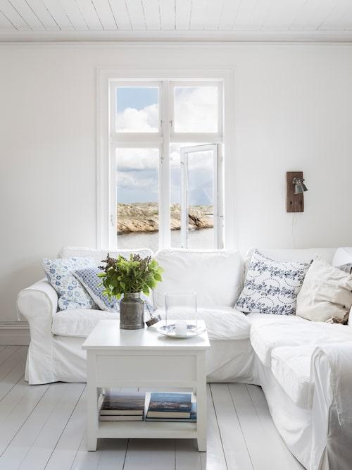 Vardagsrummet är precis som som resten av huset inrett i vitt, grått, brunt, beige och en skvätt blått – perfekt matchat med de karga klipporna och havet utanför.