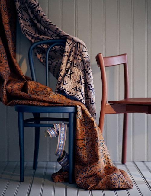 """Sveriges äldsta möbeltillverkare Gemla fabriker (1861) gör fortfarande stolar, här svarta Vienna (1907) i basad bok, oljad i kulör Blues och röda Nordic av ask, i kulör Falu. Blommig textil Marigold, i nygammal färgkombination, från Morris & co/Frank & cordinata. Mönstret ritades 1875, och nu har inredningsstudion Ben Pentreath färgsatt det med inspiration från 1960-talets färgskala. Bomullspläd Grafic recycled, från Lexington. Tapetbård rekonstruerad efter en bård från 1890-talet, hämtad från arbetarlängorna """"Svarta raden"""" vid Motalaverken. Ur kollektionen Kulturhistorisk bok, från Lim & handtryck."""