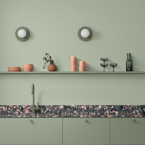 Knoppar, blandare och luckor i ljuvt grönt, ett samarbete mellan Beslag design och Toniton. Med bänkskiva i grön rosa terrazzo skapas spänning. Väggfärg 945 Lagerblad och lister i 862 Granbarr, Alcro Pashmina.