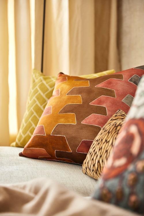Kuddar med olika mönster och storlekar ger liv till soffan, här i höstens vackra gula och rödbruna nyanser.