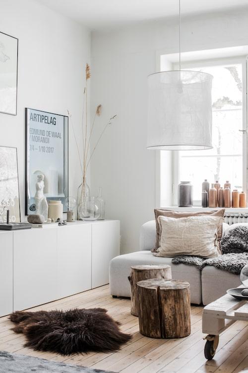 Sofies samlingar av glas, keramik och stenar illustrerar hur fint man kan skapa stilleben när man har ett flertal liknande föremål. Kubbarna från landstället funkar både som bord och extra sittplatser. Soffa, Bolia, lampa, Granit, bordet är egentillverkat.