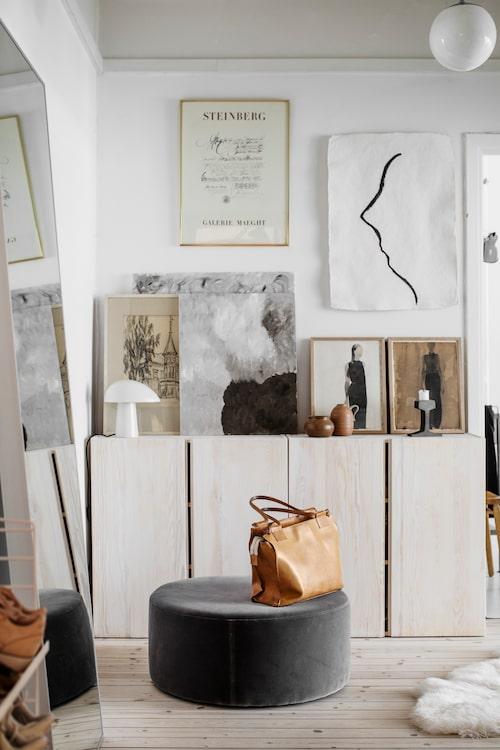 Med en samling konstverk i gemensam neutral färgskala är det enkelt att få ett harmoniskt resultat trots skilda stilar och tekniker, och oavsett om de har ram eller inte. Vitlaserade Ivarskåp från Ikea, puff, Melimeli.