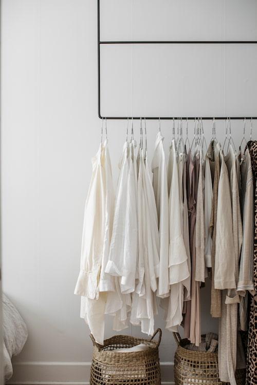 Takhängd klädhängare i stål från Anna Leena, perfekt när ytan är liten och dessutom ett dekorativt blickfång om man har en så färgstämd garderob som Sofie. Enkla stålgalgar från kemtvätten passar i den subtila, minimalistiska stilen.