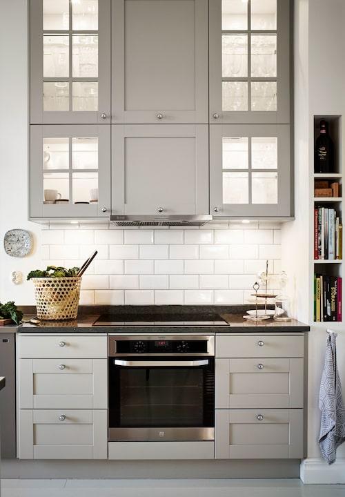 Vedumkökets Karinluckor kompletteras med vitrinluckor Stina med inbyggd belysning. På väggen en liten Rörstrandstallrik med motiv från västgötaslätten.
