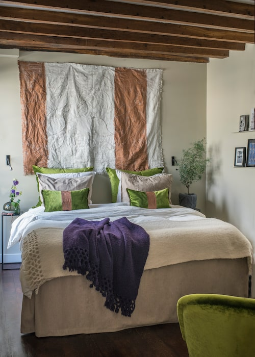 """Sängen är från österrikiska Pauly, som gör handgjorda sängar av naturmaterial. """"Det är lavendel invävd i den"""", säger Charlotte Rosenberg Bosten. De gröna kuddarna har hon klätt med grönt sammetstyg från Christian Lacroix. Den breda randen har hon målat med kopparfärg på linne."""
