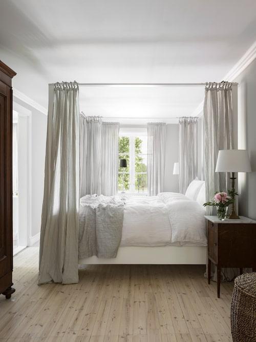 Parets vackra sovrum pryds av en romantisk himmelsäng med sängram, köpt på Blocket. Sängbordet är inropat på auktion.