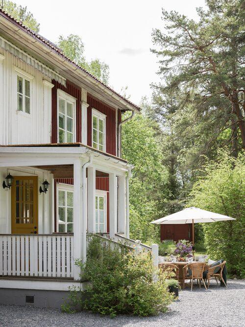 Det faluröda huset byggdes i början av förra seklet i den gamla bruksorten Borgvik. Utanför huset har paret anlagt en uteplats där måltidena intas under sommarhalvåret. Bord från Bruket Interiör, rottingfåtöljer, Ikea. Köket har också fått en rejäl omgörning. Väggar togs ner för att skapa yta och fönster i gammal stil har satts in. Barstolar, Ellos Home.