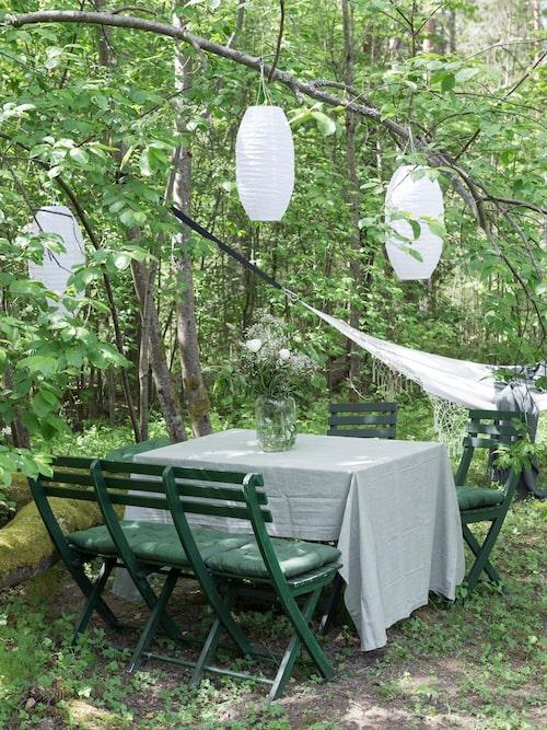 Under träden finns en skönt skuggig uteplats alltför varma dagar. Solcellslyktor från Ikea, Möbeln är köpt på Blocket och ommålad med grön linoljefärg.