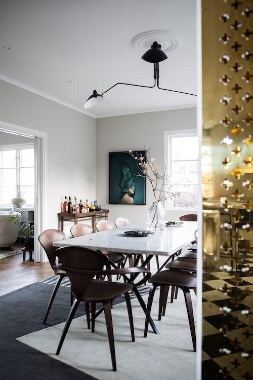 Matsalsbordet med skiva i marmor har plats för tio sittande och är formgivet av Per Söderberg/No early birds. Stolar från Cherner. Möblemanget är för övrigt sparsmakat så att det är lätt att röra sig i rummet, här är ofta bjudningar och kalas. Tavla av konstnären Amy Judd.
