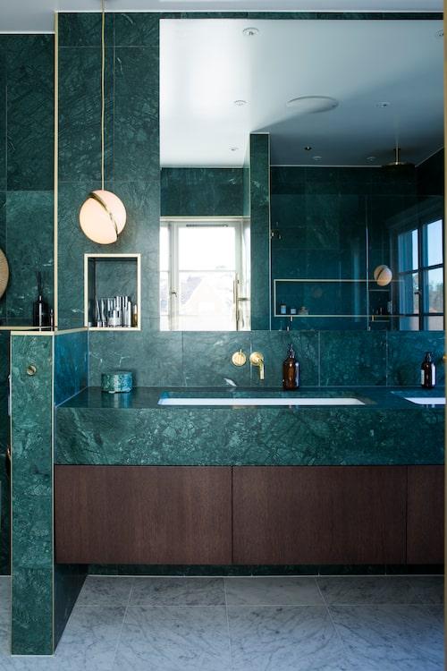 """Badrummet är helt klätt i italiensk grön marmor. """"Vi har sett det vita överallt och ville ha något helt annorlunda, dessutom är allt annat så beige och dovt i huset – så badrummet som också är stort, gav oss utrymme att tänka lite annorlunda."""""""