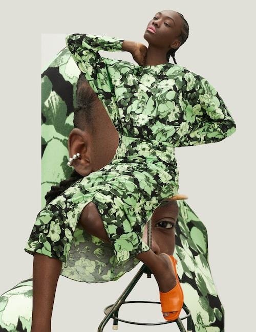 Blommig klänning av viskos/elastan, 3275 kr, Lovechild. Orange slip-ins av lammläder, 4000 kr, Acne Studios. Earcuff av sterling silver, 1195 kr, C by C.