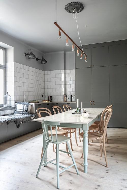 De franska bistrostolarna är från Brandstationen. Lamporna på väggen är danska vintagelampor, och matbordslampan är Jonas Bohlins Star 6 i koppar från Örsjö belysning. Den inbyggda sittbänken vid köksfönstret är en specialitet som Katarina och Andreas försöker rita in i alla lägenheter de arbetar med.