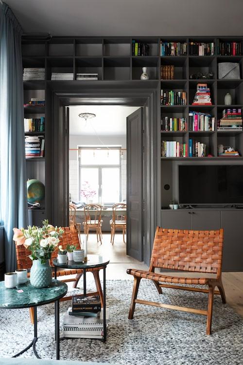 Bokhyllan i vardagsrummet är byggd av köksstommar från Ikea och mdf-skivor. De danska fåtöljerna med sits i flätat läder är från Brandstationen. Bord med grön marmorskiva från H&M Home.