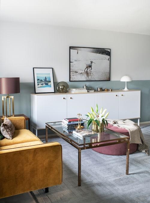 På nedre plan finns ett kombinerat vardags-  och arbetsrum. Soffan kommer från Andreas farföräldrars hem, soffbordet är ett loppisfynd. Byrån från Ikea har pimpats med ny bänkskiva och nya beslag. Rosa puff från Layered.