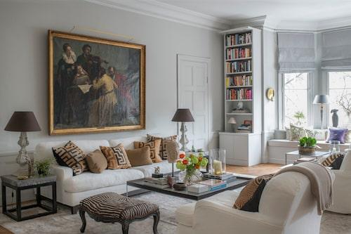 Jugendvåningens generösa takhöjd och vardagsrummets storlek bidrar till den välkomnande känslan. Stora omfamnande sittmöbler och en dominerande antik målning får ta plats. Soffa och fåtöljer, Jio möbler, sideboard och kuddar, Walles & Walles, matta, Knut mattor, zebramönstrad pall, Oscar & Clothilde, soffbord, Ligne roset. Bokhyllan är platsbyggd av Odd job.