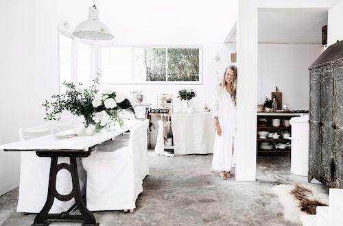 Rå plywood och en bit tyg har använts för att skapa ett provisoriskt köksskåp. Virgine älskar plåtskåp – det här är från en antikhandel, precis som matbordet och den franska taklampan. Soptunnan i metall är från The Society Inc som drivs av den kända inredningsprofilen Sibella Court.