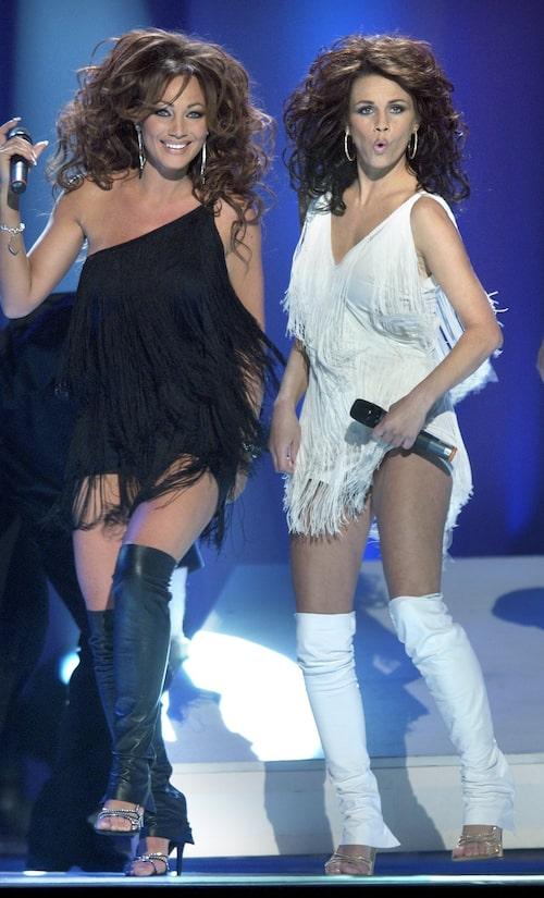 """Programledarna Charlotte Nilsson och Lena Philipsson uppträder vid deltävlingen i Melodifestivalen 2003. Klänningarna var skapade av Marina Kereklidou. """"Jag minns att Lena absolut ville ha den vita, så det fick bli svart för mig."""""""
