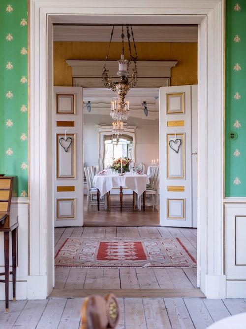 Från empiresalongen blickar man in i den gula salongen och vidare in i matsalen vars spegelklädda kortvägg dubblerar intrycket av våningen. Empiresalongens djupgröna tapet med dekor av gyllene bin är inspirerad av Joséphine Bonapartes sovrumstextil.