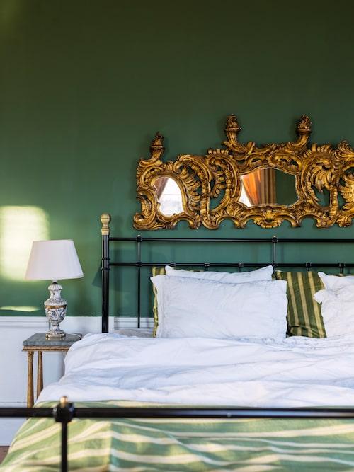 Sängramens strama linjer mjukas upp med ett förgyllt överstycke i nyrokoko.