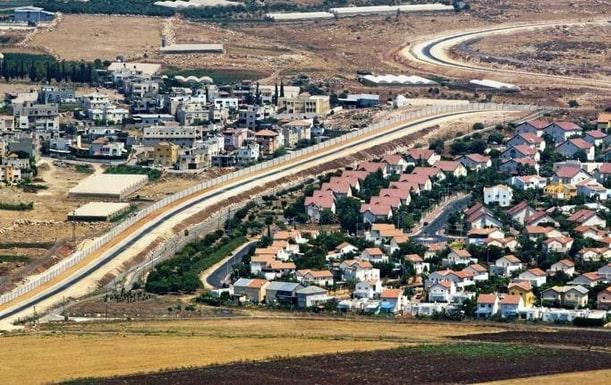 En palestinsk by (till vänster) separeras från en israelisk bosättning på Västbanken av den skyddsmur Israel har byggt på ockuperat område. Nya beslut om bosättningar den senaste tiden har försvårat processen mot en tvåstatslösning, skriver Margot Wallström.