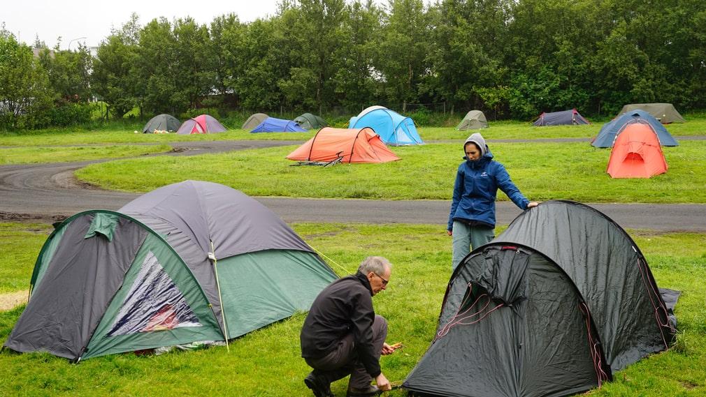 2 juli 2018, schweiziska turisterna Etienne och Celine Evéquoz ser till att under en massivt grå himmel förankra sitt tält på campingplatsen Laugardalur i Reykjavik.
