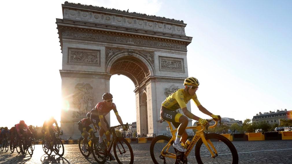 Colombianen Egan Bernal i den gula ledartröjan passerar Triumfbågen i Paris.