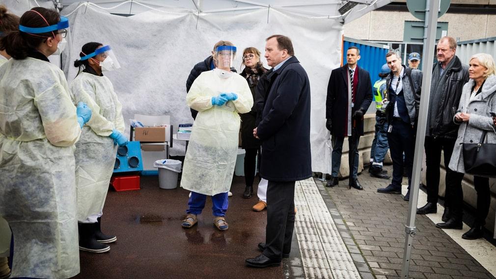 Funktionsledare Helena Gisslén lättar på munskyddet för att statsminister Stefan Löfven ska höra bättre. Innan nästa patient måste all utrustning ändå bytas ut enligt de strikta rutinerna.