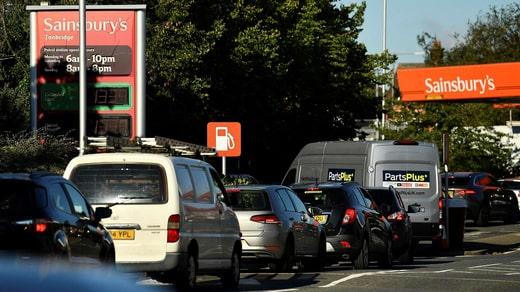 Lunghe code in una stazione di servizio a Tonbridge, nel sud-est dell'Inghilterra, venerdì.  Il governo ha esortato le persone a non farsi prendere dal panico.