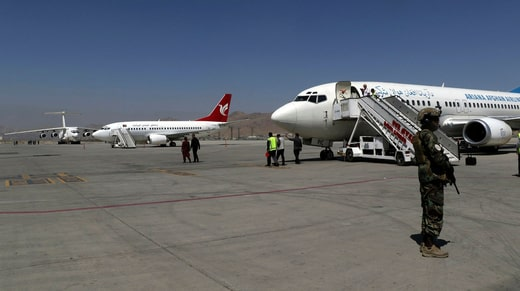 A gunman stands next to a plane at Kabul airport.